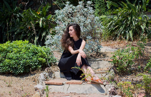 Isabella Frappier Los Angeles Doula Woman Sitting Stones Green Plants Flowers